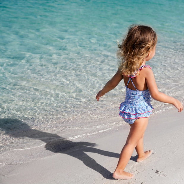 girl at the beach wearing sunuva baby girl liberty print swimsuit