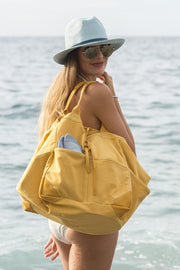 woman on the beach with yellow Travaux en Cours tote bag over her shoulder