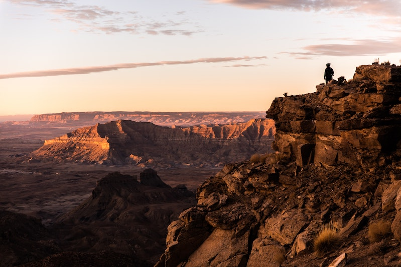 Person stands on overlook of canyon