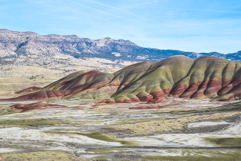 Colorful earth mounds with mountain in background and blue sky