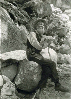 John Muir Sitting on Rocks
