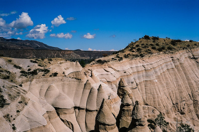 Cone-shaped tan hoodoos beneath a blue sky.