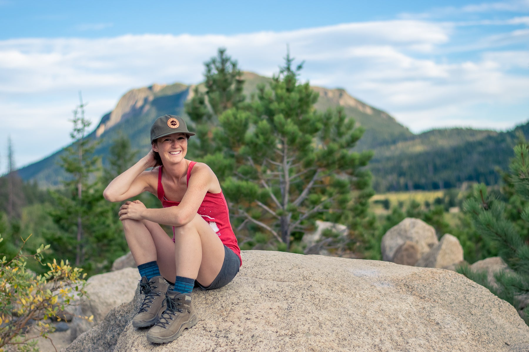 Woman wearing Spruce Classic Wild Hat on gray boulder with green mountains in background.