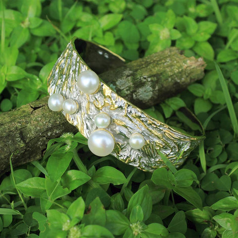 Silver bangle with rough surface, fresh waterpearls, touched with gold