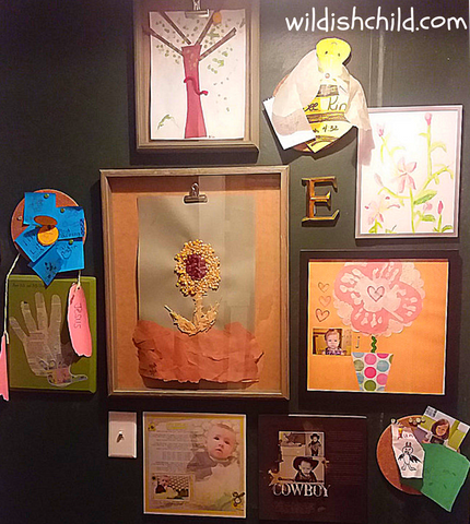 wildish child displaying children's art in the home black background gallery wall with kids art and pictures
