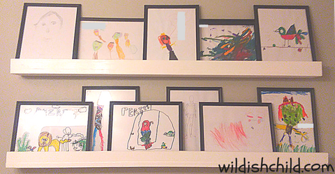 wildish child displaying children's art in the home white picture ledges with kids art in the bathroom
