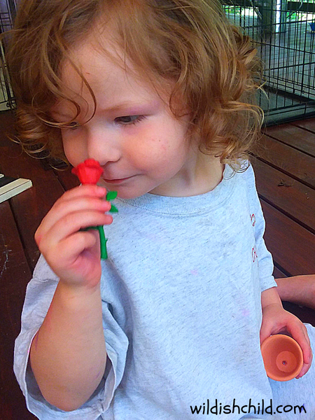 wildish child flower sensory bin smelling a fake rose