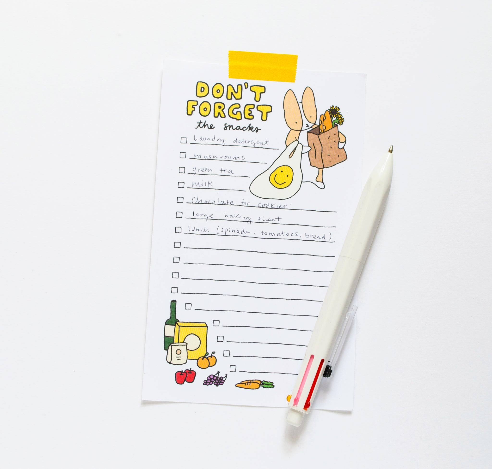don't forget snacks market notepad with corgi holding grocery bags and groceries on the bottom, styled with pen