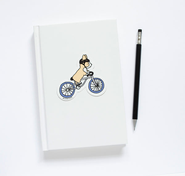 corgi riding bicycle sticker on a notepad