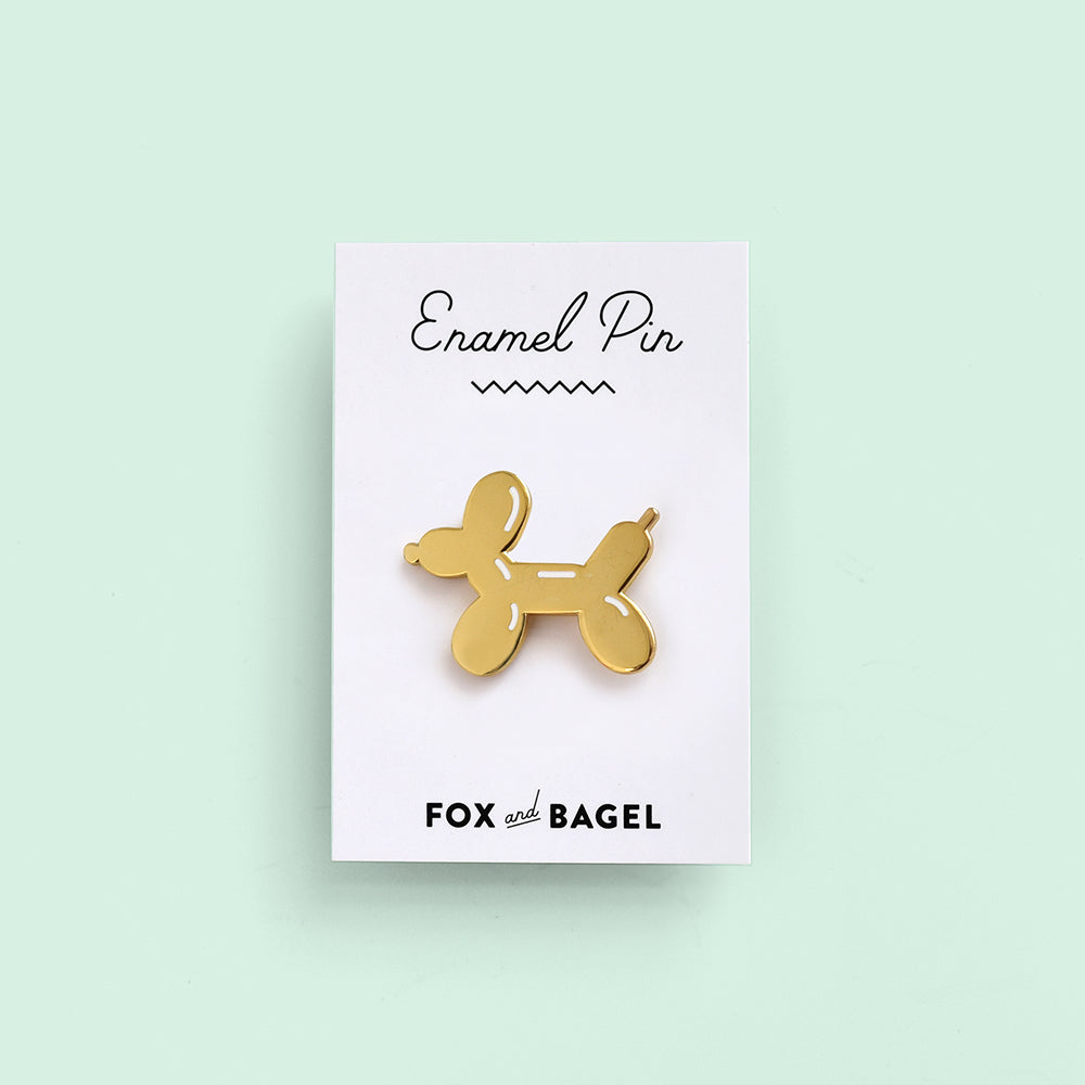 Gold balloon dog hard enamel pin by Fox & Bagel.