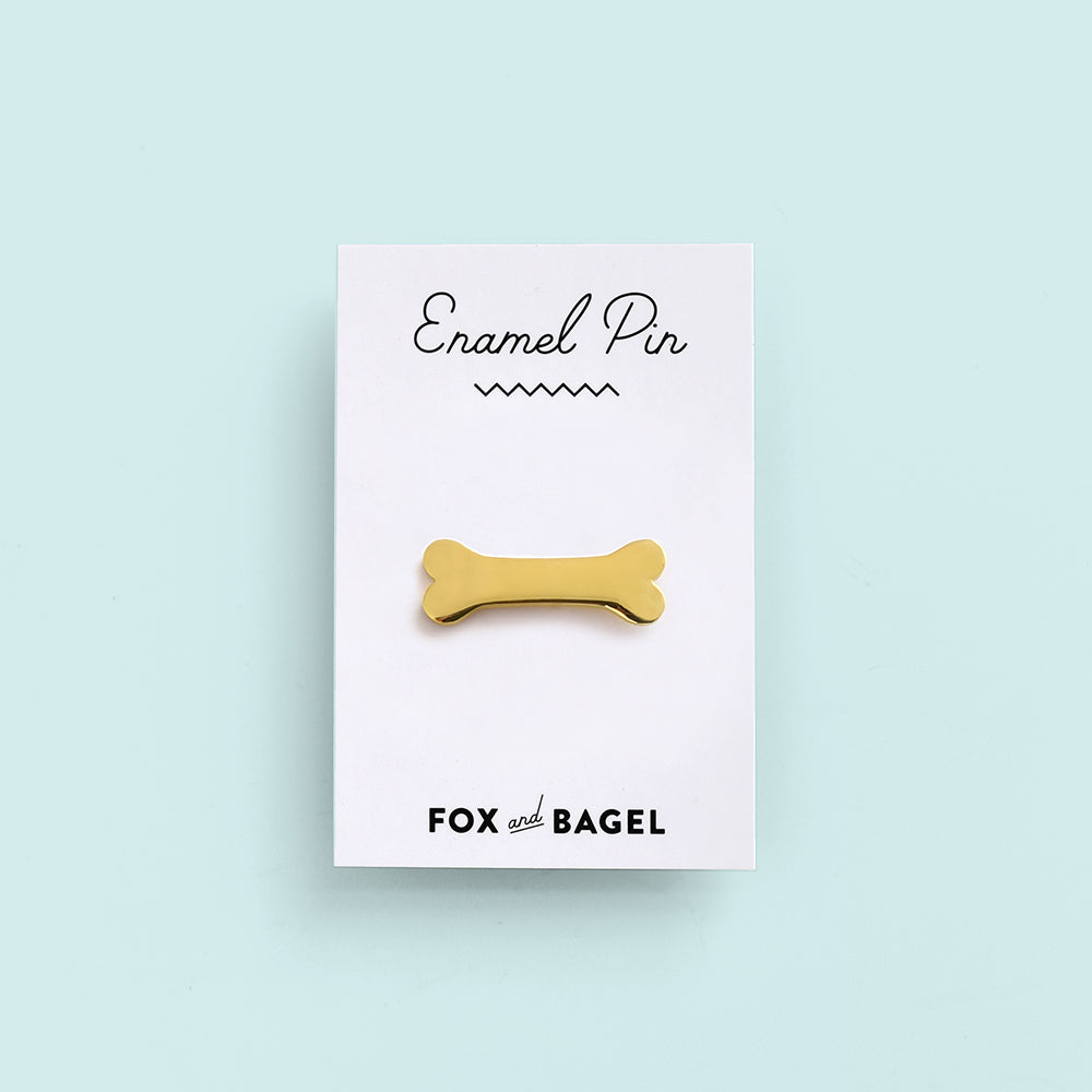 Gold dog bone enamel pin by Fox & Bagel.