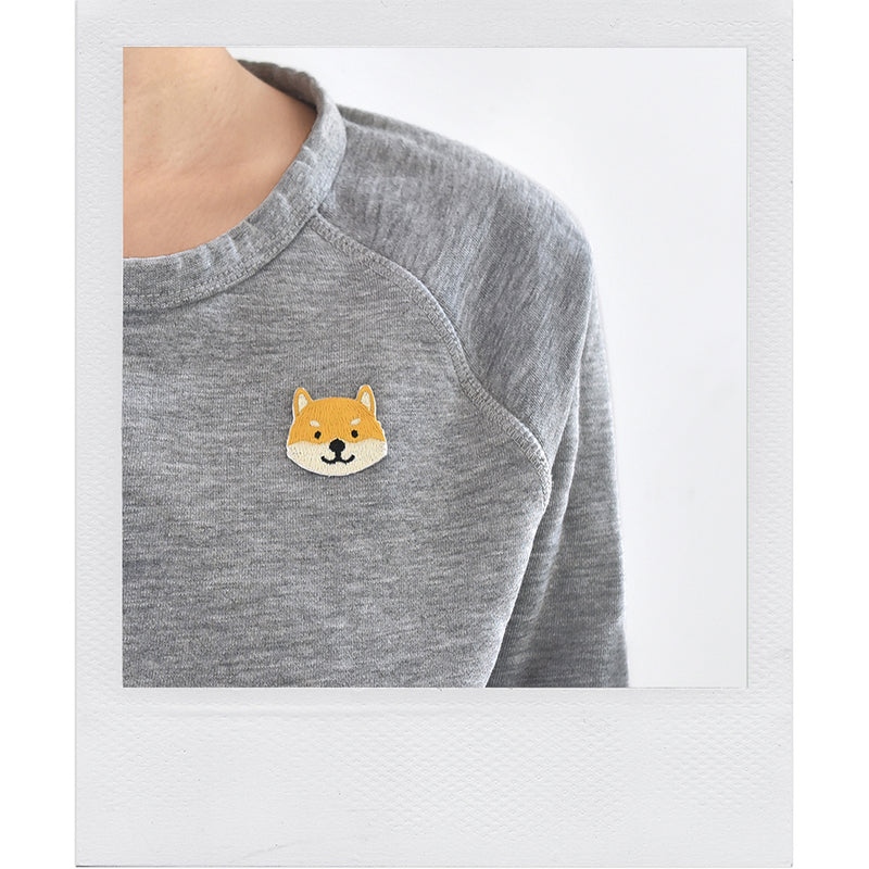 The Shiba Inu dog embroidered sticker patch by Fox & Bagel looks great on a gray sweatshirt.