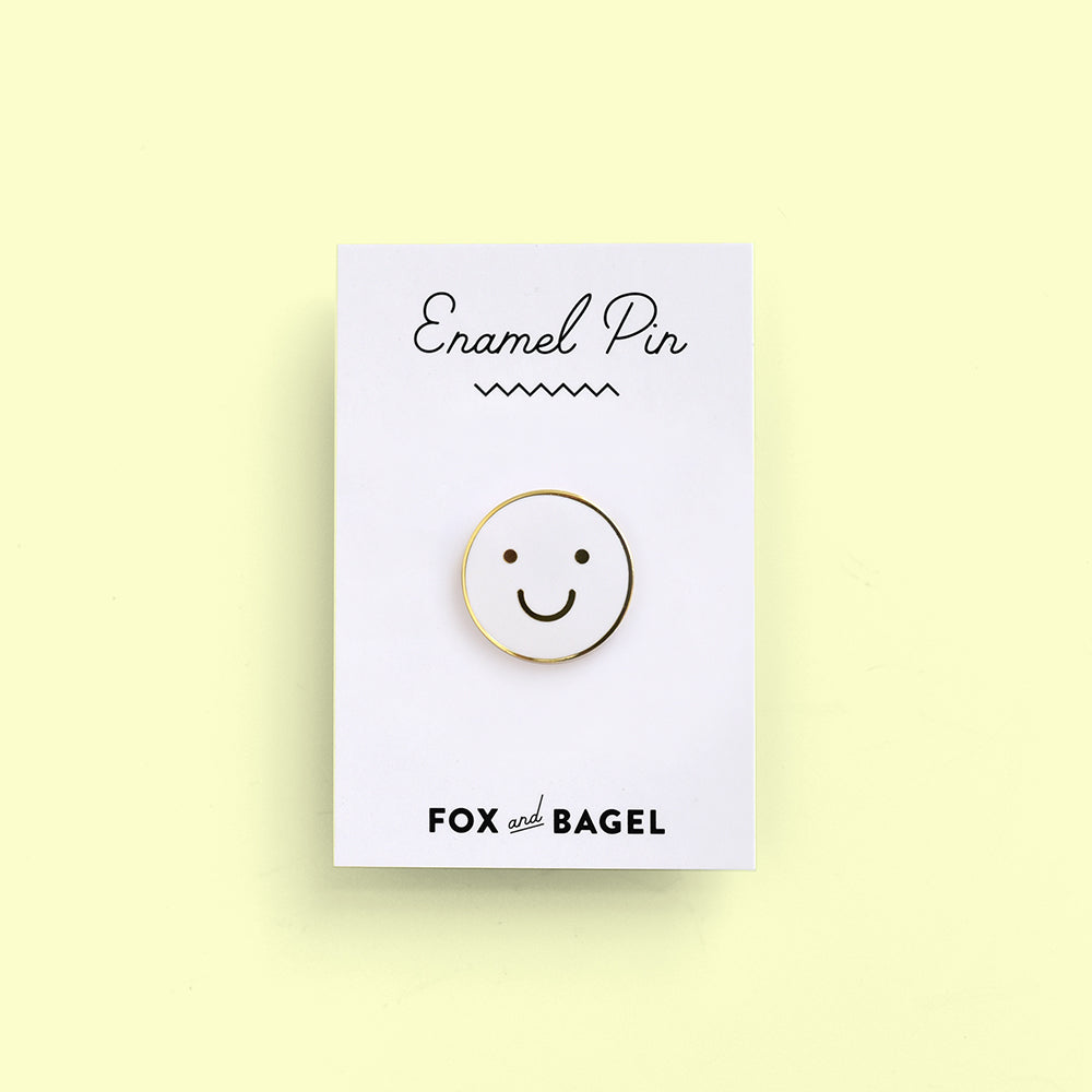 Gold happy face enamel pin by Fox & Bagel.