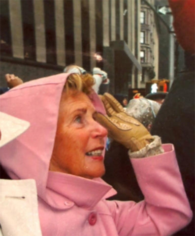 woman looking up with pastel pink raincoat on and tan gloves with hand up holding hood