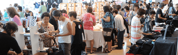A busy craft show with people browsing different vendors.