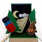 The centre piece of the card with a black background, stars, the moon, evergreen trees, camping bag, tent, and camp fire.