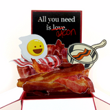 "The centre piece of the card with a black background, an egg with a smiley face, bacon strips, and text saying ""all you need is love BACON"". The word ""love"" is crossed out."