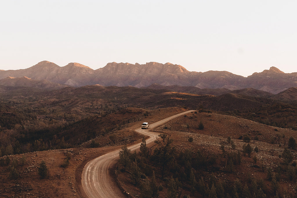 Ariel view of vintage van driving along an s-bend dirt road