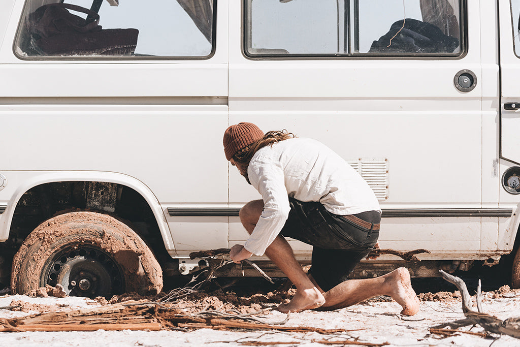 Driver wearing Levi Copper beanie attempts to fix mud covered tyre