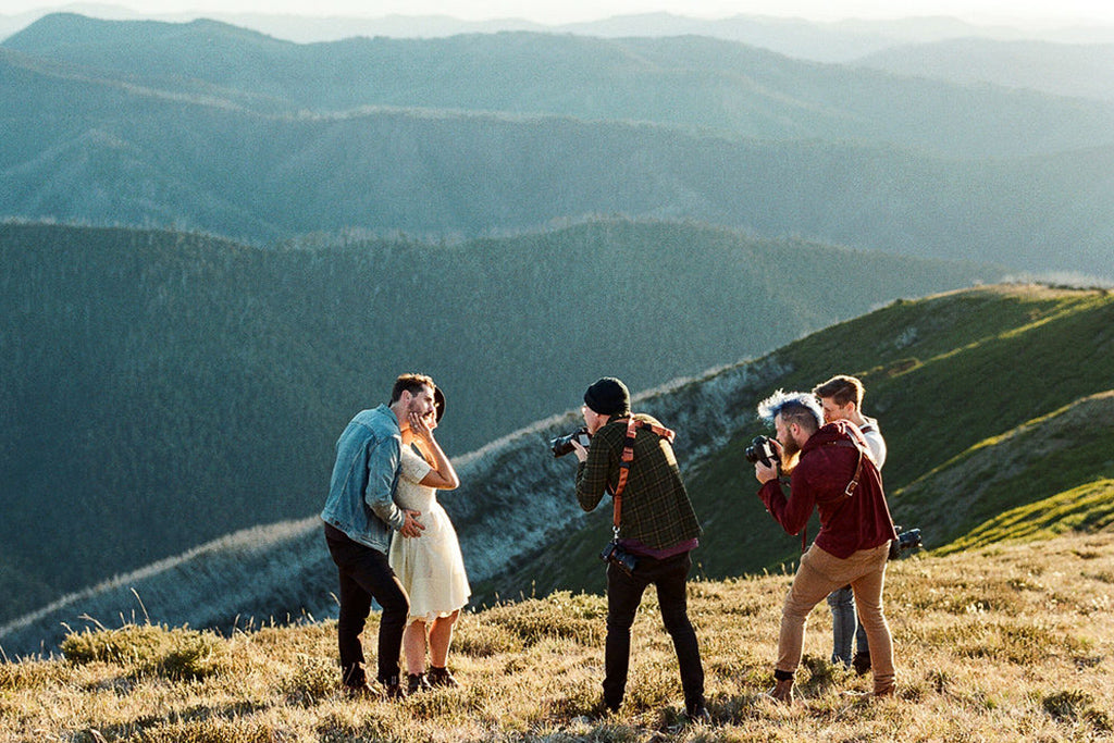 Male and female couple pose in front of a photography group on top of a mountain