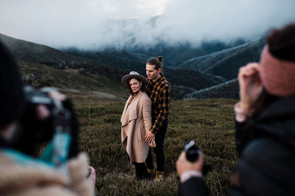 Male and female couple pose in front of a misty valley whilst group of photographers capture their image