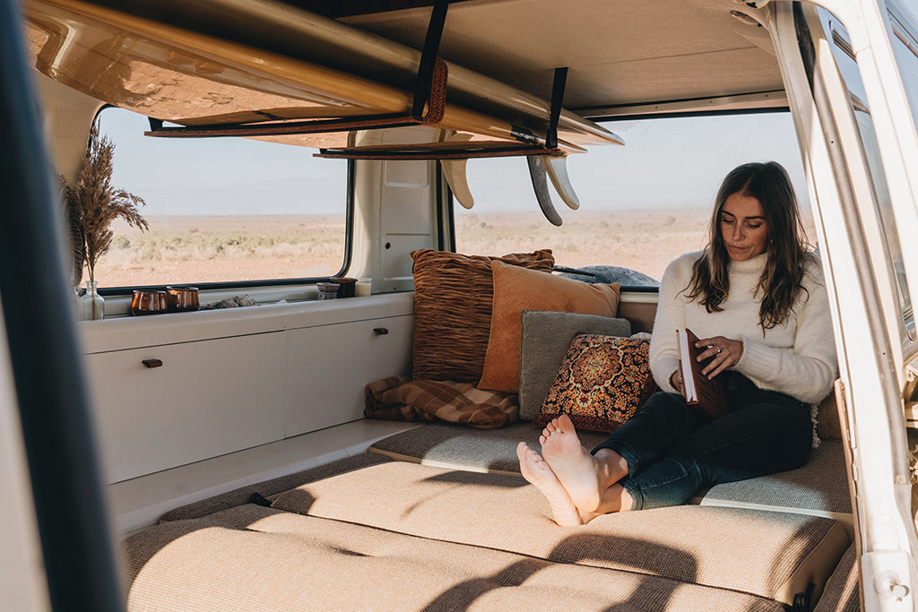 Female sits on her newly restored vintage van couch reading a book