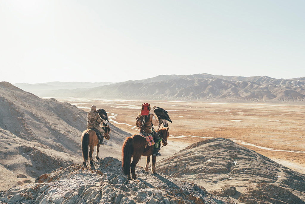 Mongolian tribe leaders on horseback with hunting eagles on forearm looking out to panoramic views of their land