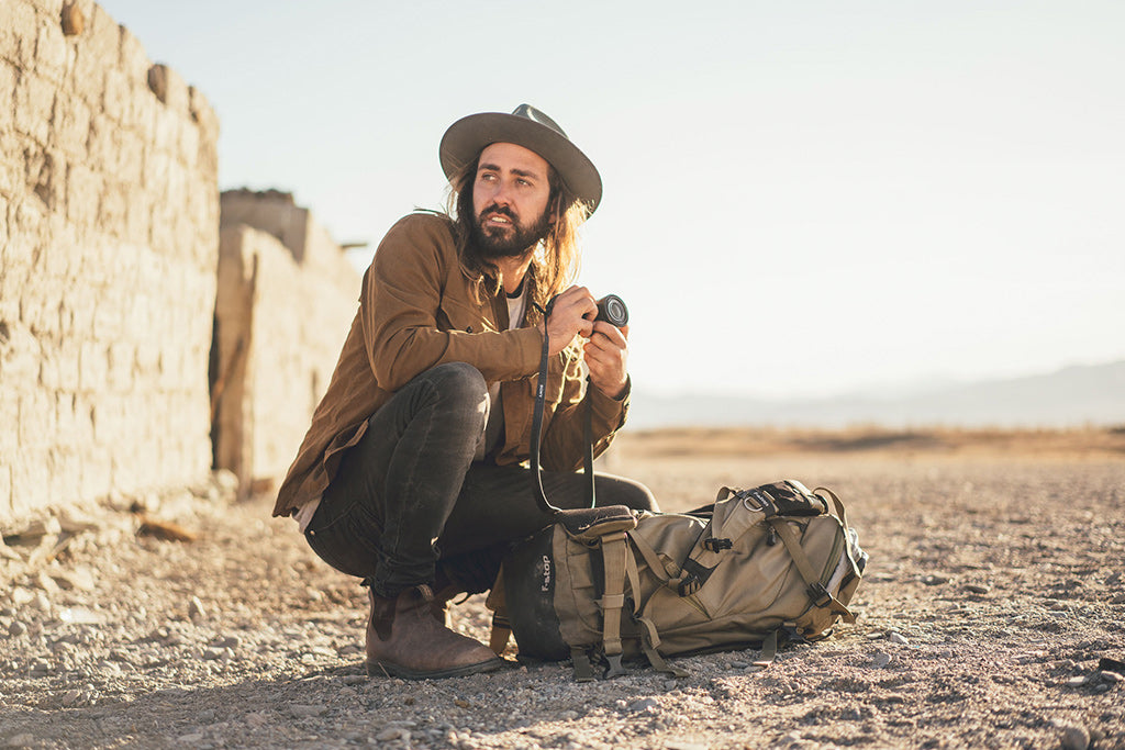Stefan Haworth crouches down with camera in hand wearing Calloway Fawn Hat