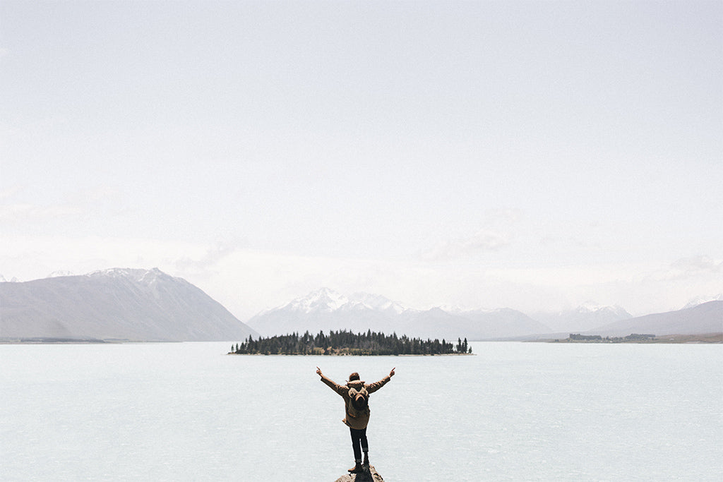alt='male stands on rock with arms in air overlooking an island of trees in Lake Taupo New Zealand''