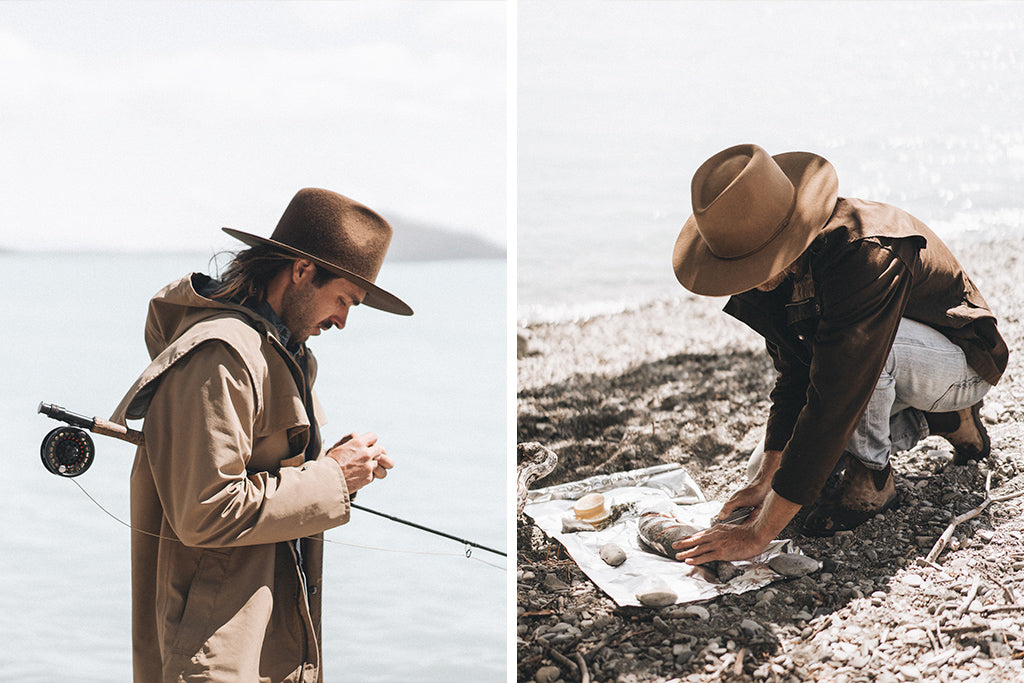 alt='fishermen in Andy Auburn and Andy Oak hats catching and preparing fish to eat by the lake'