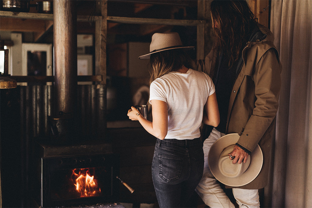 alt='couple wearing wide-brim hats stand around a cabins indoor fireplace with a cup of tea'