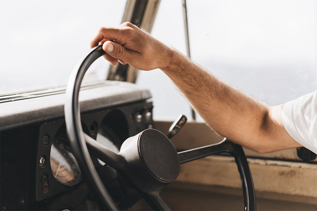"alt=""Stefan Haworth driving his vintage land cruiser with hand on steering wheel"""