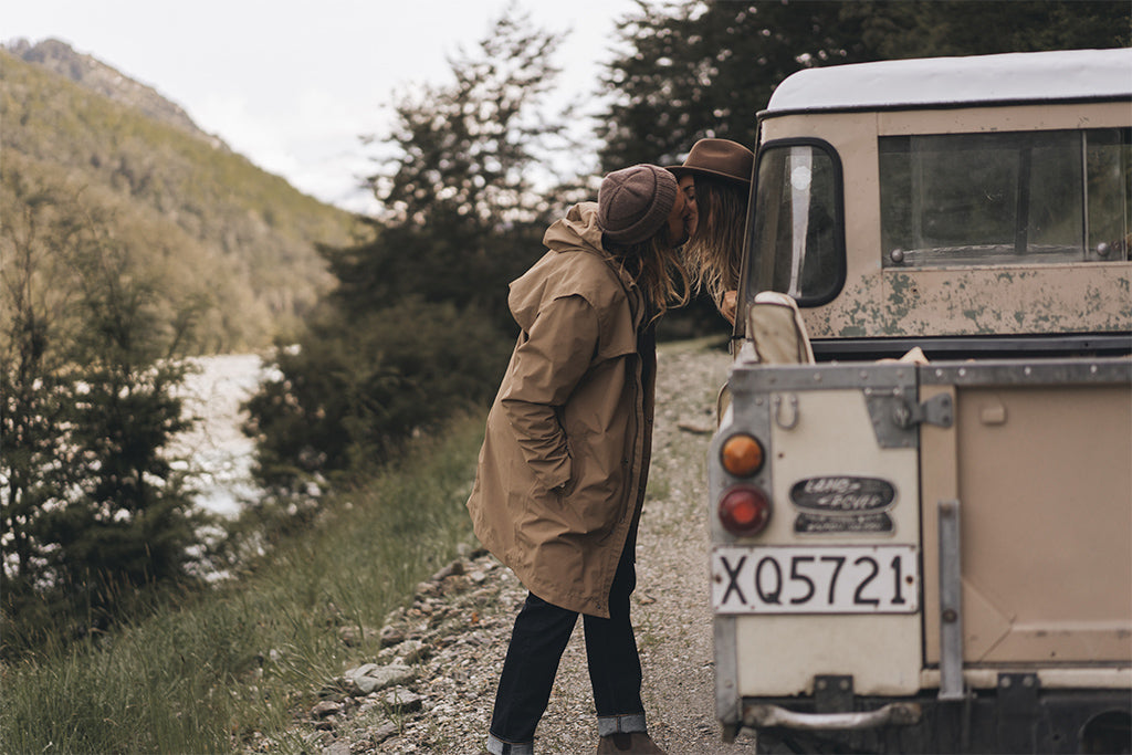 "alt=""Founders of Will & Bear in the Tasman Brown beanie and William Brown hat kissing out side of parked vintage land cruiser in New Zealand"""