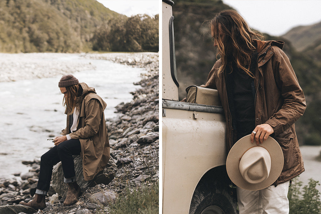 "alt=""Alex from Will & Bear in brown Driza-Bone jacket and beanie by river bed in New Zealand using pocket knife"""