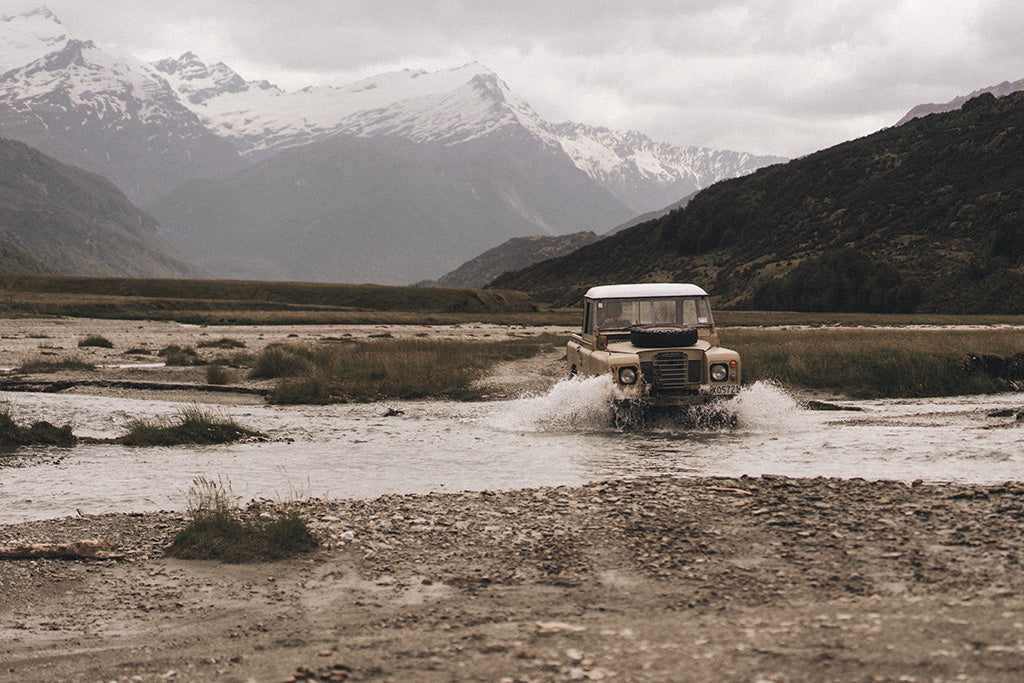 "alt=""Stefan Haworth driving vintage land cruiser through river crossing with snow capped mountains behind"""