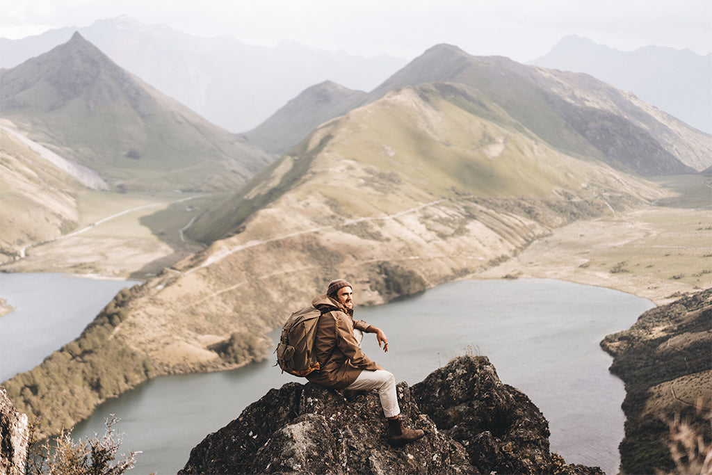 alt='hiker wearing Will & Bear Tasman Brown beanie and Brown Driza-Bone jacket sits on rock at summit overlooking the lake and valley below'