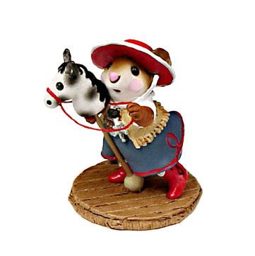 Cow girl riding a toy horse