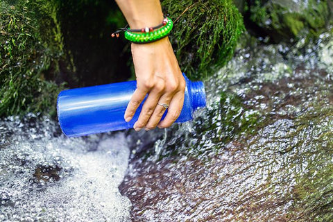 hiker filling up water bottle with fresh water outside