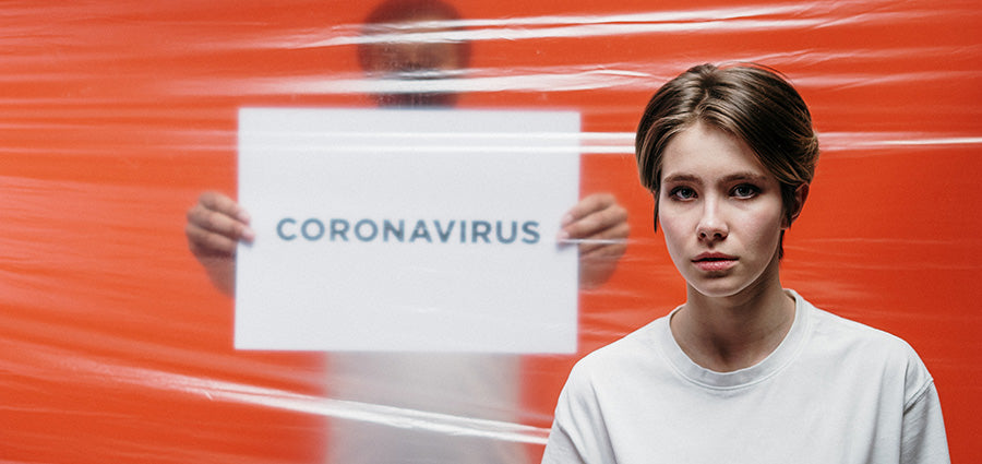 Man holding a coronavirus sign. how to use cbd oil for stress and anxiety.