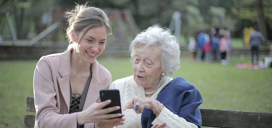 Woman with elderly mother looking at smartphone. Does cbd oil work for pain? How to use cbd oil for back pain. How long does it take for cbd oil to work for joint pain?