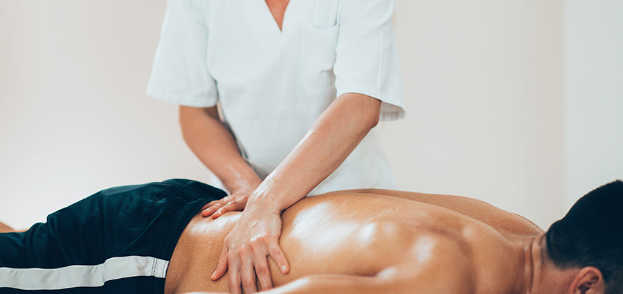 Adult man getting a back rub with CBD oil. Buy massage oil with CBD online.