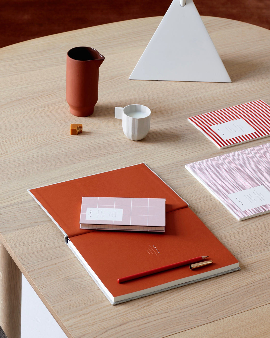 NOTEM studio stationary, simple design, oak table, pink notebook and weekly planner