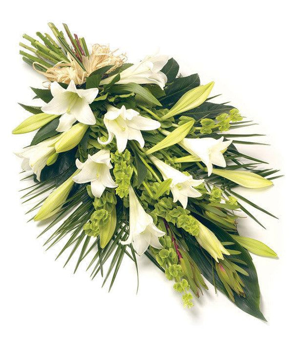 Flowers for funerals: A classic white Lily hand tied sheaf. Longiflorum Lilies and an array of foliage tied with a natural raffia bow.