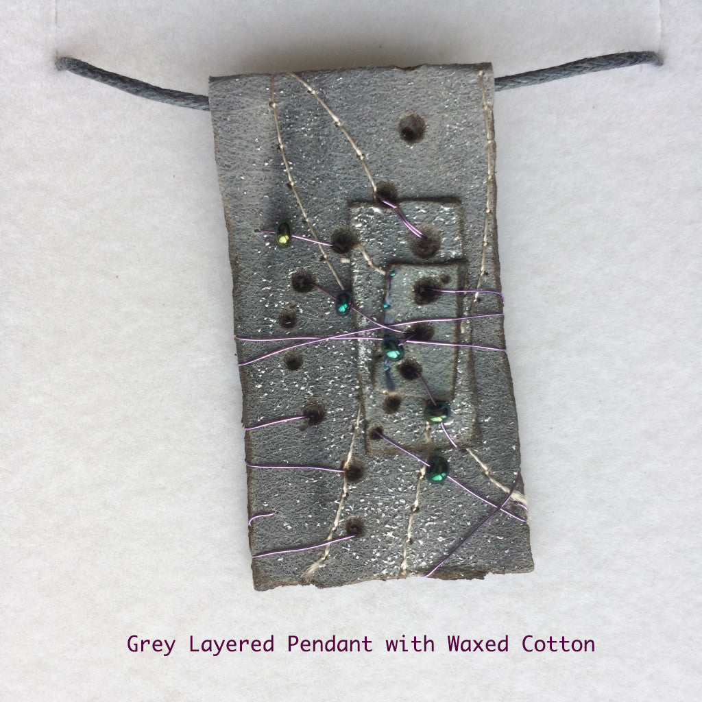 Grey layered pendant with waxed cotton tie.