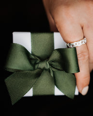 hand holding a jewellery box packaged with a safari green bow