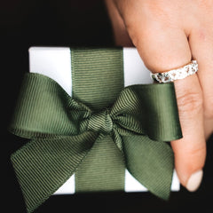 hand holding a little jewellery box with a ring on the finger