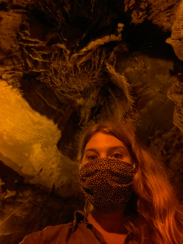 Aubrey exploring a cave, wearing her ABD Culture rubber, adventure jewelry.