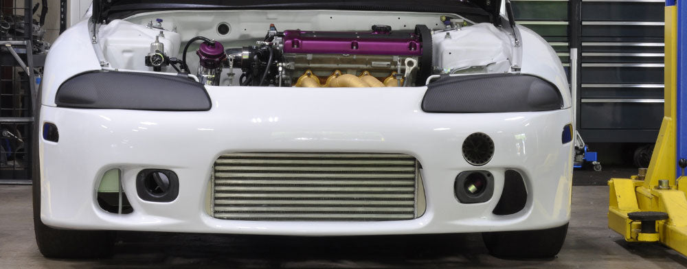 1998 white gsx with forward facing turbo, purple valve cover and gold coated exhaust manifold.