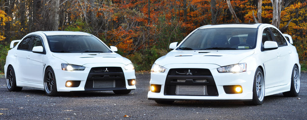 Two white Evo Tens with STM front mount intercoolers installed, RPF1 wheels and Nokya Yellow fog lights.
