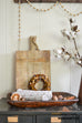 farmhouse style wooden cheese board with fall preserved wreath